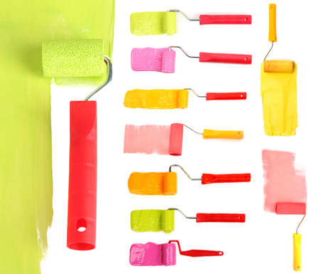 Roller brushes with color paint isolated on white photo