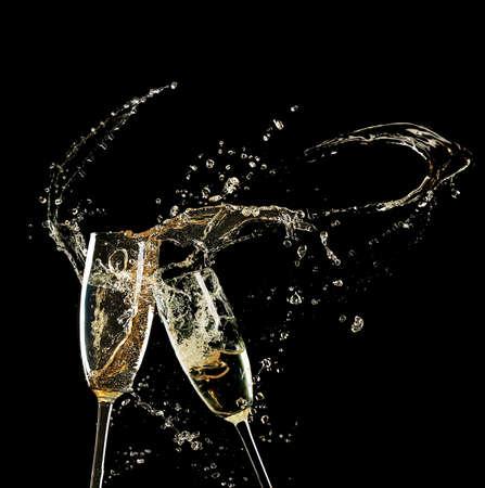 Glazen champagne met splash op zwarte achtergrond
