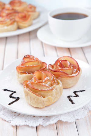 Tasty  puff pastry with apple shaped roses on plate on table close-up photo