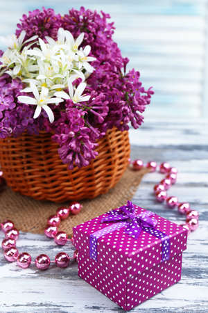 Beautiful spring flowers in wicker basket on wooden table, close up photo