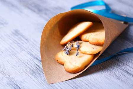 Lavender cookies in paper bag, on color wooden background photo