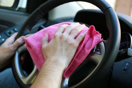 Hand with microfiber cloth polishing car photo