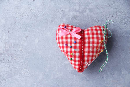 Fabric heart with color pins on color wooden background photo