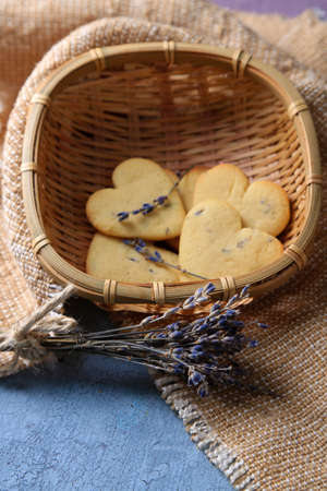 Lavender cookies in wicker basket, on sackcloth, on color wooden background photo