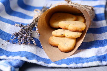 Lavender cookies in paper bag, on color napkin background photo