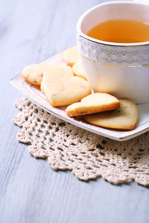 Lavender cookies and cup of tasty tea on color wooden background photo