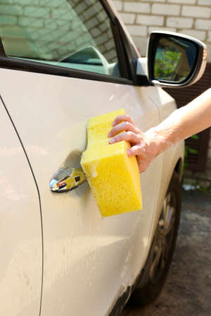 Outdoor car wash with yellow sponge photo
