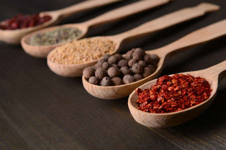 Different spices in spoons on wooden background photo