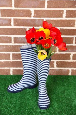 rain boots: Composici�n de tulipanes de colores en las botas de lluvia en el fondo brillante Foto de archivo