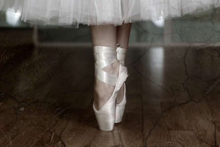 pirouette: Ballerina legs in pointes in dark dancing hall Stock Photo