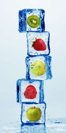 Ice cubes with fruits and berries on light background photo