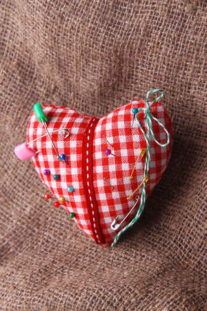 pinhead: Fabric heart with color pins on sackcloth background