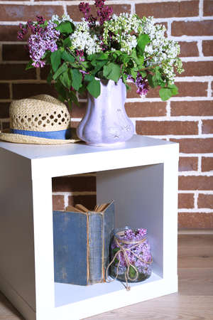 Beautiful Lilac Flowers In Vase On Stand On Color Wall Background