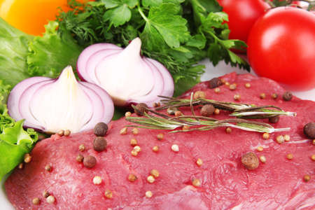 Raw beef meat with vegetables on plate close up photo