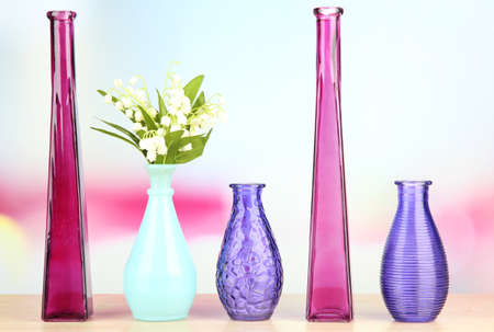 Different decorative vases on shelf on light background photo