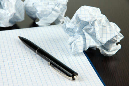 Crumpled paper balls with notebook and pen on wooden background photo