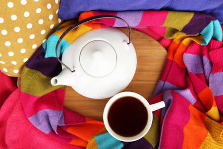 Cup and teapot on wooden stand and scarf on bed close up photo
