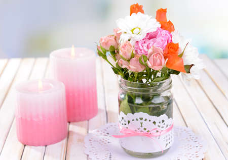Beautiful bouquet of bright flowers in jars on table on light background photo