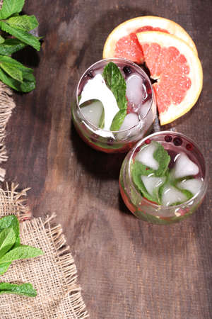 Tasty cocktail with fresh grapefruit and mint leaves on wooden table background photo