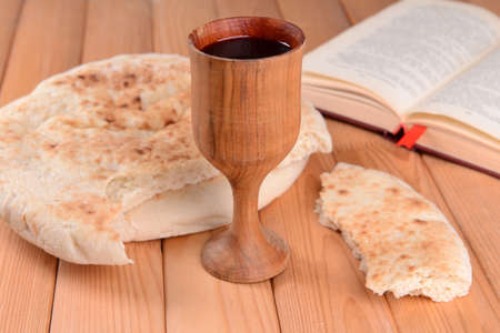 last supper: Cup of wine and bread on table close-up