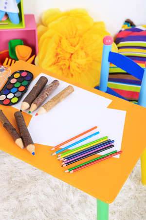 nurser: Interior of classroom at school. Crayons and paper on table Stock Photo