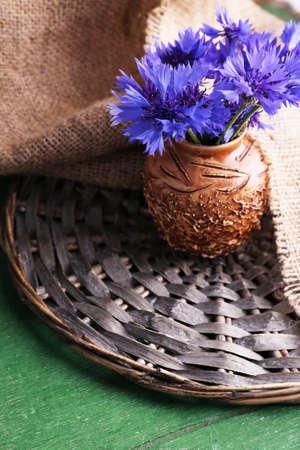 Beautiful cornflowers in vase on wooden background photo