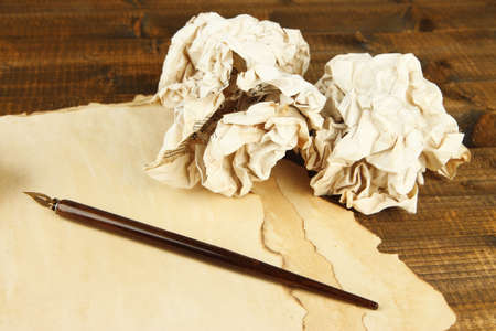 Crumpled paper balls with ink pen and envelopes on wooden background photo