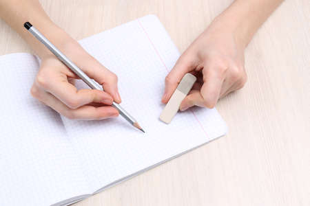 Human hands with pencil writing on paper and erase rubber on wooden table background photo