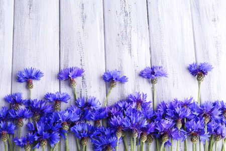 Beautiful cornflowers on wooden background photo
