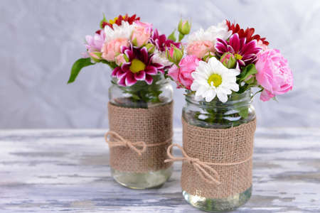 Beautiful bouquet of bright flowers in jars on table on grey background photo