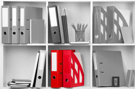 Concept of individuality.One color shelve with stationery among grey shelves with stationery