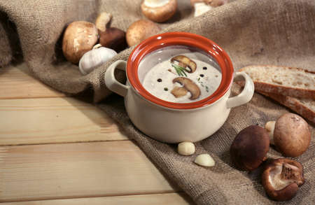Mushroom soup in pot,on napkin,  on wooden background photo
