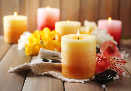 Hermosas velas con flores sobre fondo de madera