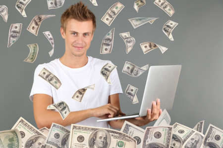 Young man working on laptop with money rain on grey  photo