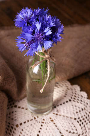 Beautiful cornflowers in glass vase on wooden background photo