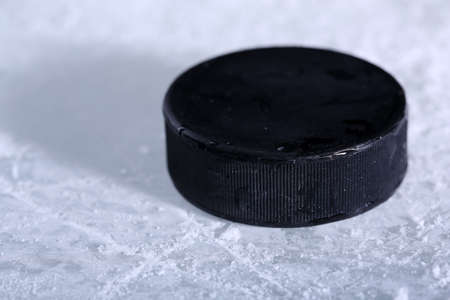 hockey puck: Black hockey puck on ice rink background