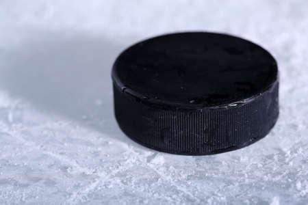 hockey puck: Black hockey puck on ice rink background
