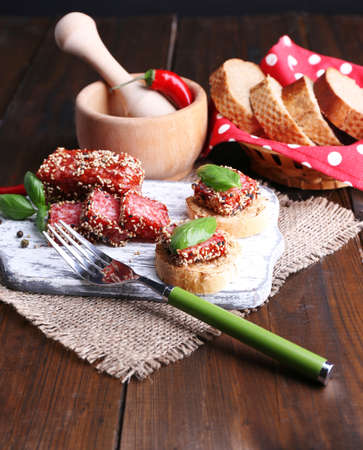 Composition with knife,  tasty sandwiches with salami sausage, basil leaf on cutting board, on wooden background photo
