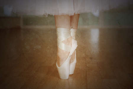 Ballerina legs in pointes in dancing hall photo