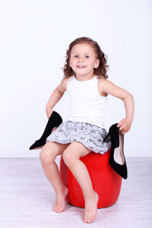 Beautiful small girl in big shoes sitting on leather ottoman on wall background photo