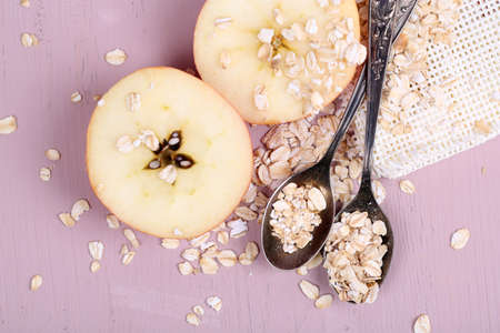Apple with oatmeal and vintage spoons, on color wooden background photo