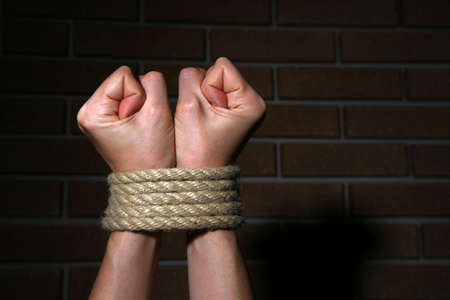captivity: Tied hands on dark background