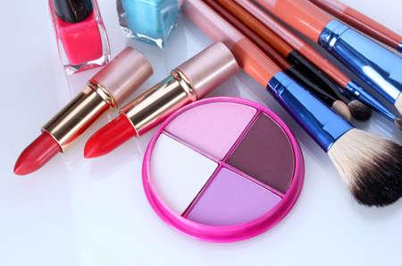 productos de belleza: pinceles de maquillaje y cosméticos en el soporte aislado en blanco