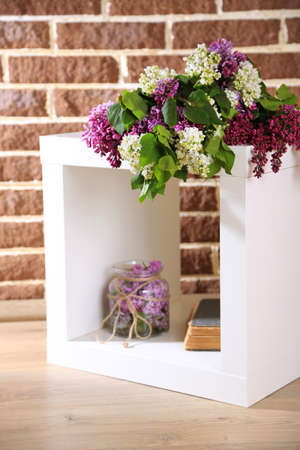 Beautiful lilac flowers in wicker basket, on stand, on color wall background photo