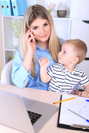 Pretty woman with baby working at home photo