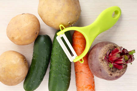 Peeler and raw vegetables on wooden table photo