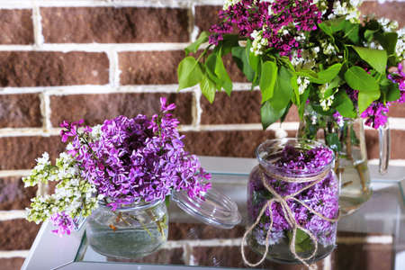 Beautiful lilac flowers in vase, on table, on color wall background photo