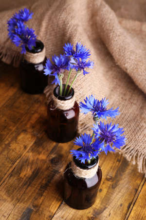 Beautiful cornflowers in glass bottles on wooden background photo