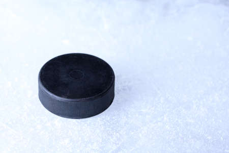 Black hockey puck on ice rink background photo