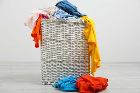 Full laundry basket  on wooden floor on gray background